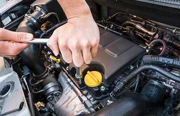 Mechanic turning socket wrench on engine